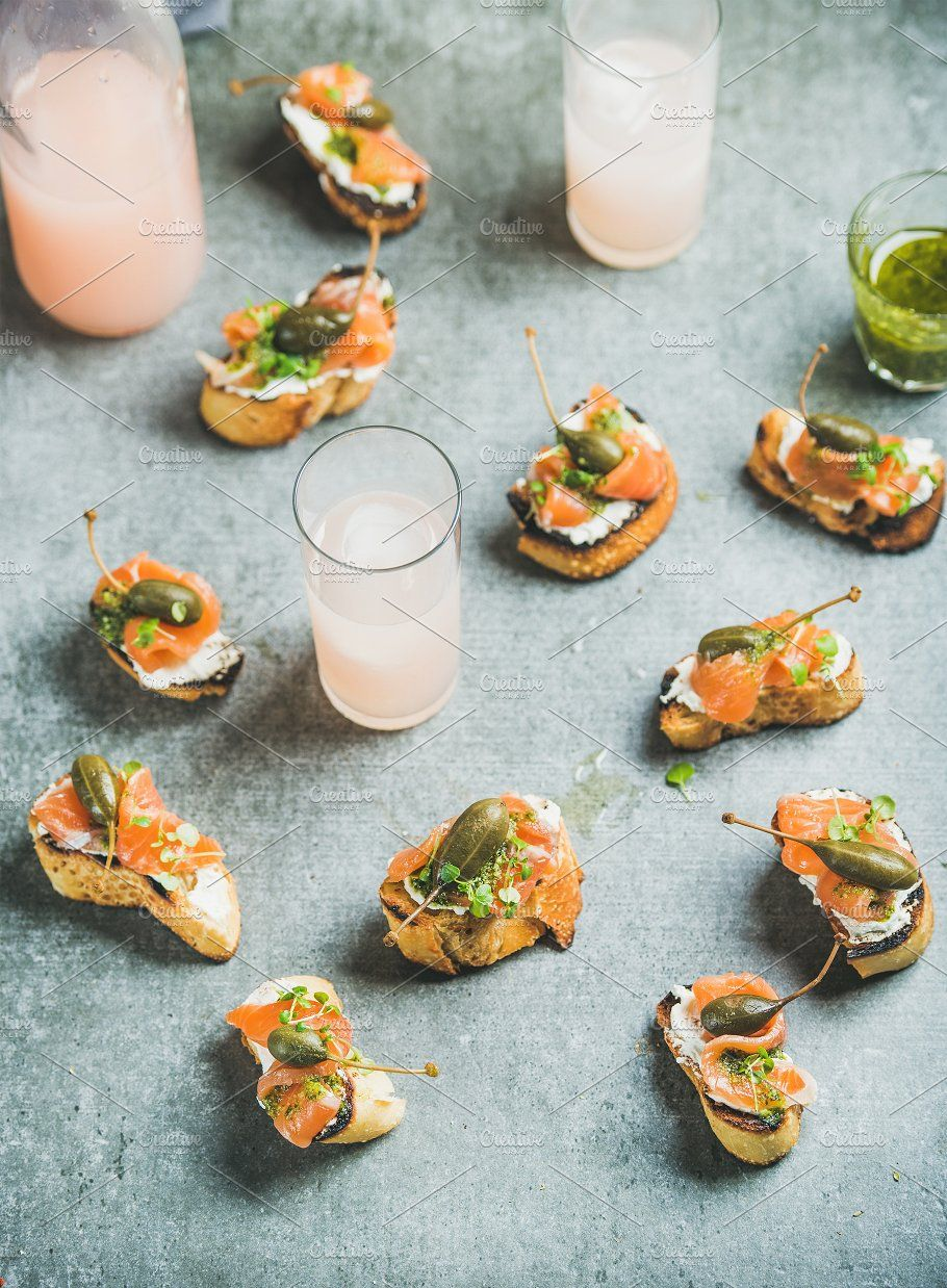 #Crostini with smoked salmon and grapefruit cocktails in glasses  Crostini with smoked salmon pesto sauce watercress and capers and pink grapefruit cocktails over grey background. Party catering or fingerfood concept #grapefruitcocktail