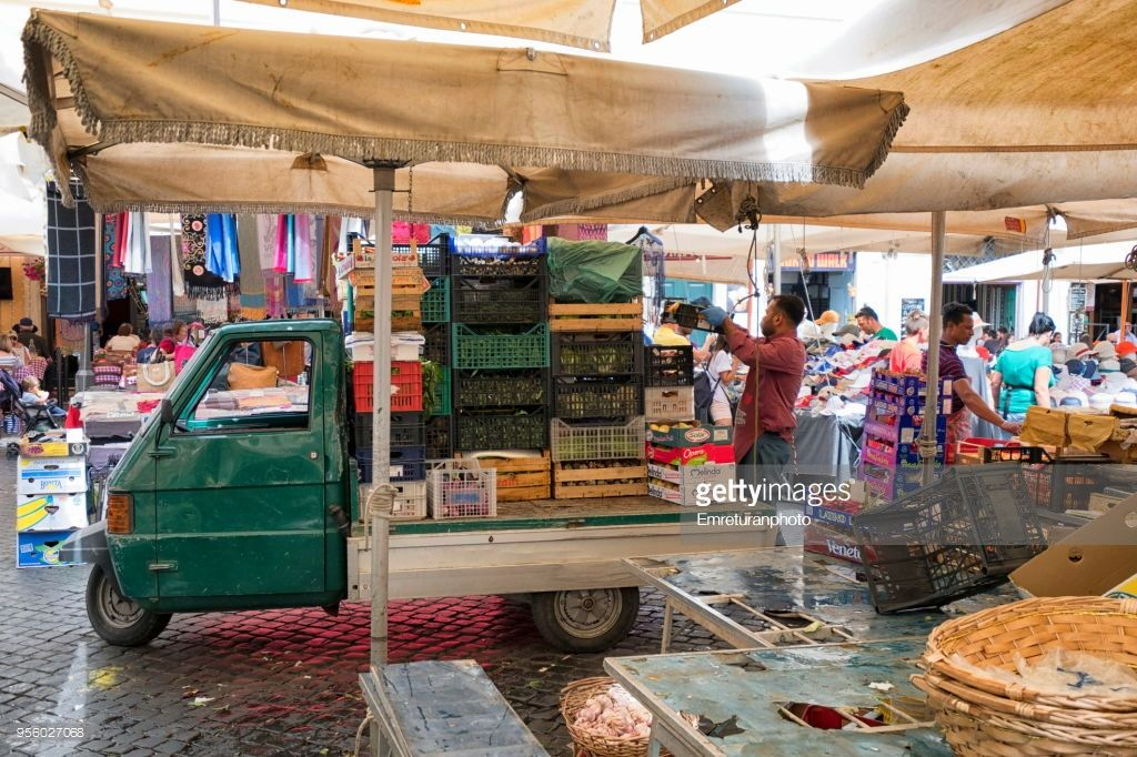 a man unloads grocery stuff to vendors from the triporter while