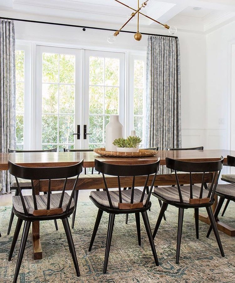Midcentury modern dining room with a vintage rug, a chandelier, and