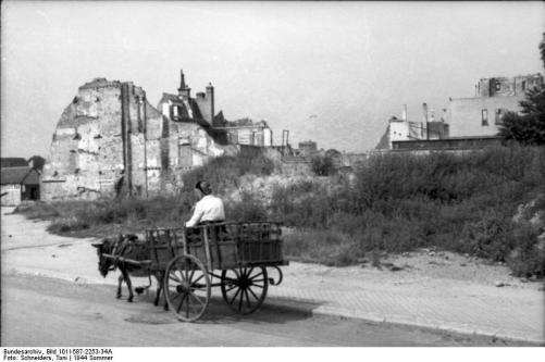 Toni Schneiders, Frankreich, Eselskarren vor zerstörten Häusern in der Normandie. Aufnahme: Sommer 1944