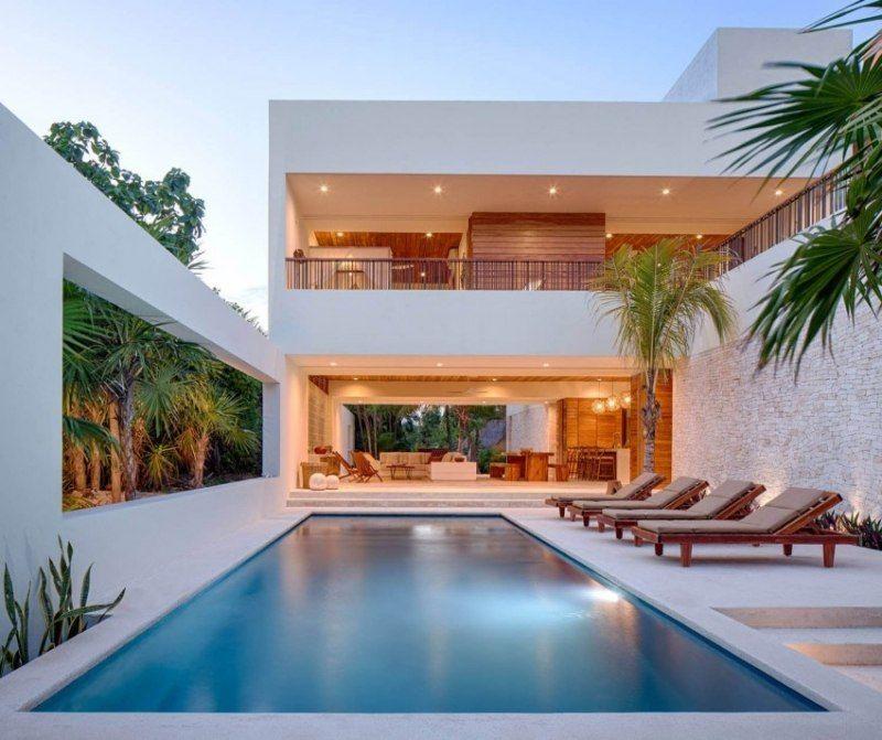 Jardin moderne avec piscine rectangulaire enterrée avec plage carrelée et chaises longues en bois