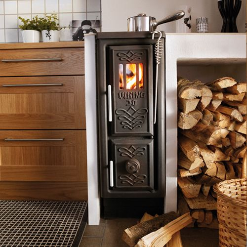 Small Viking wood stove built into kitchen with firewood supply next to it.  Looks like - Small Viking Wood Stove Built Into Kitchen With Firewood Supply