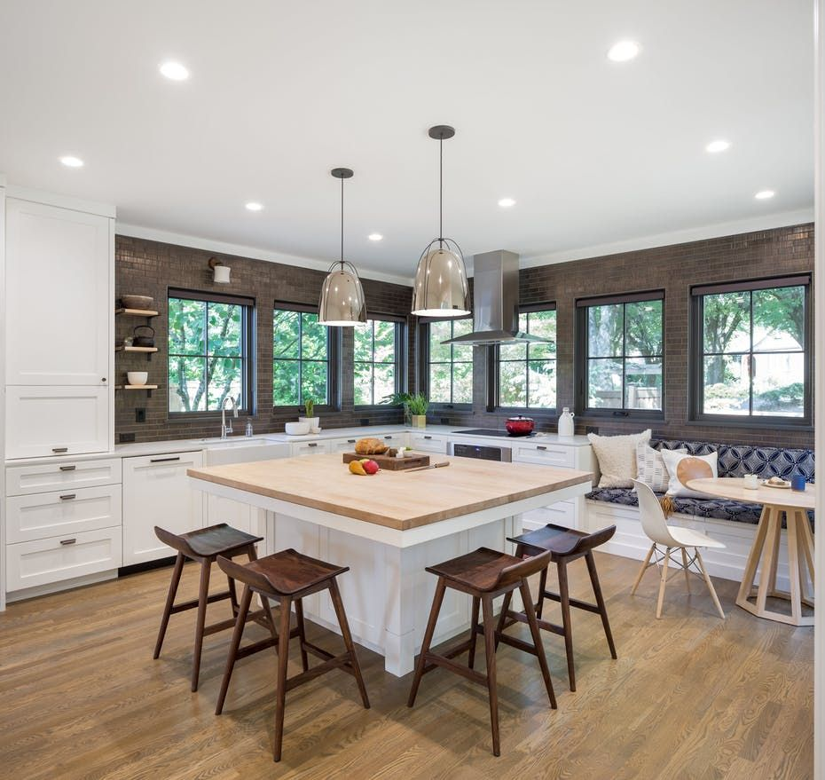 Woodblock island and a cozy banquette complete the kitchen look by ...