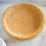 Graham cracker crust #homemadegrahamcrackercrust A homemade graham cracker crust baked in a clear pie pan, on a white marble board. #homemadegrahamcrackercrust