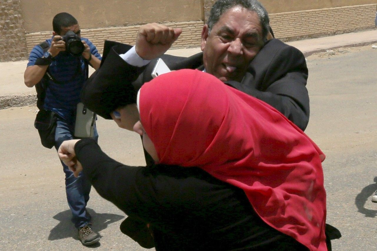 A fight breaks out between defense lawyers and family members of victims outside a court in Cairo on Tuesday, as 11 men received death sentences for their part in deadly violence that erupted at a football stadium in 2012. MOHAMED ABD EL GHANY/REUTERS