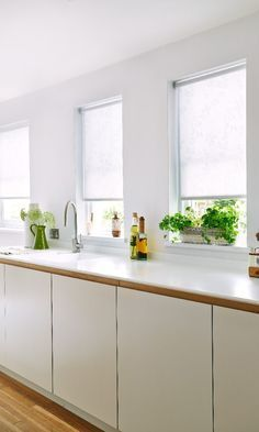 White and wood create the perfect minimalistic look. Herbs and green plants can add a little bit of colour.