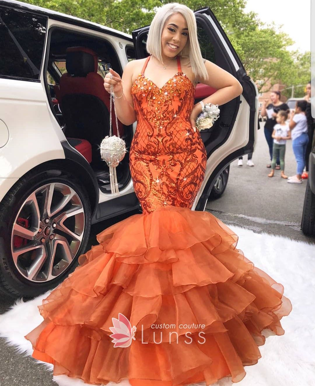 50ed196bdebc Sparkling orange sequin bodice and tiered organza trumpet floor length prom  gown with halter straps and V neckline.