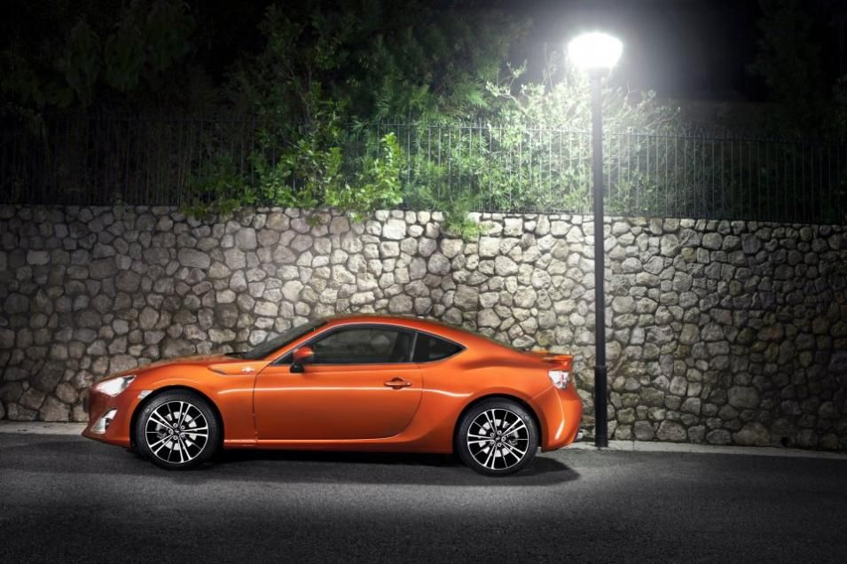 A 3d animation of a nice orange Toyota 86 next to a street