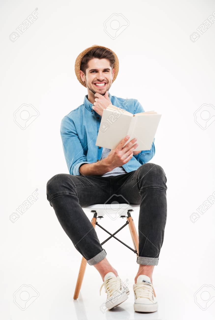 Happy Attracive Young Man Sitting On Chair And Reading A Book Man Sitting Hats For Men Books To Read