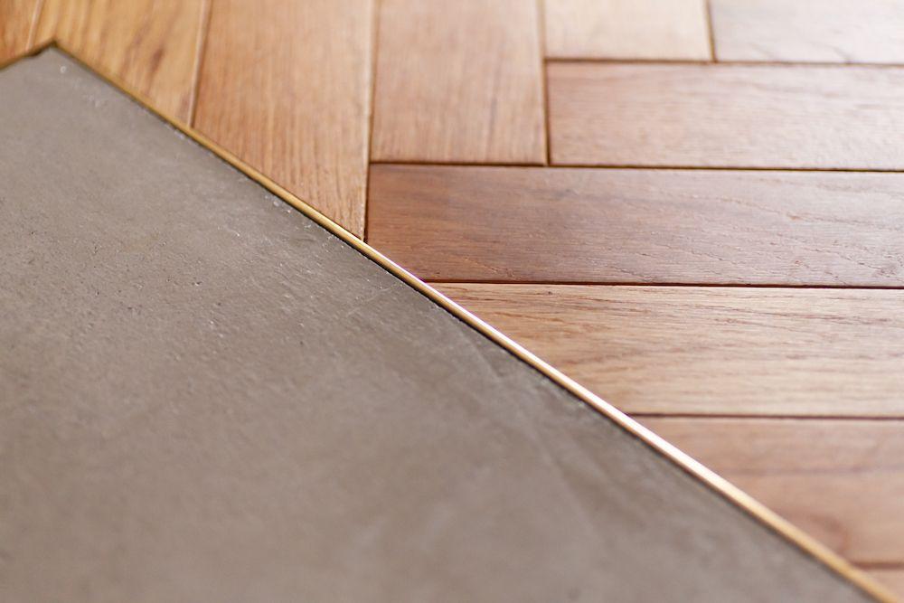 ヘリンボーンのフローリングとモルタル床の間に 真鍮製の床見切りを