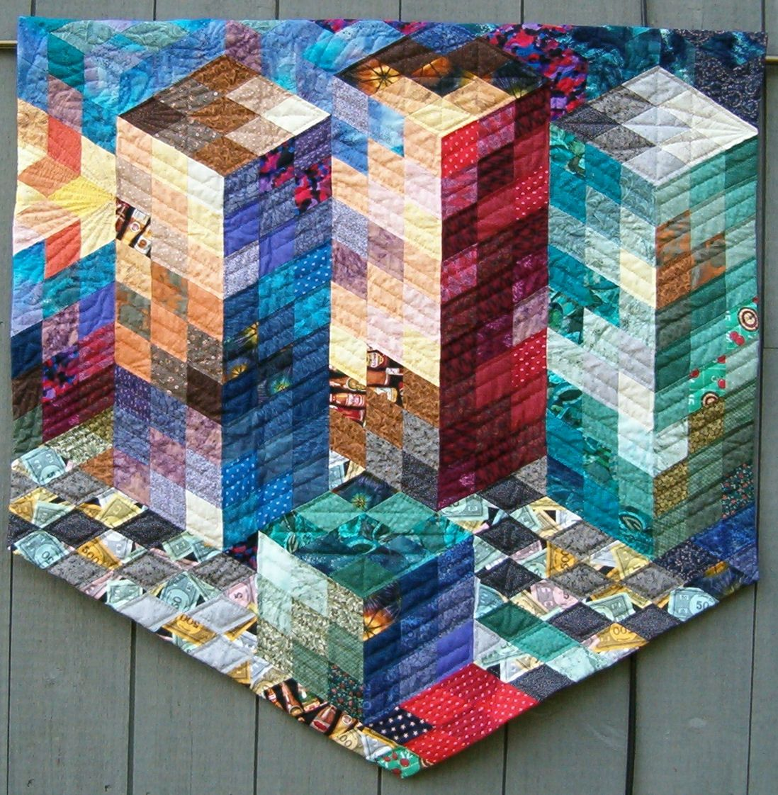 """""""Sunset on Wall Street"""" By Linda Jean Peterson.  Hand Pieced using Jinny Beyer's """"Fragmented Block"""" technique which utilizes the 60° Diamond and Color Values to achieve the three dimensional affect.  It is Hand Quilted and is in a Private Collection"""