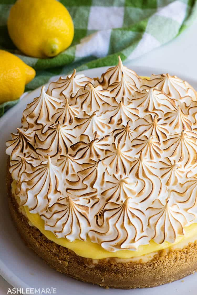 A recipe and video for the perfect lemon meringue cheesecake - a lemon cookie crust, a creamy cheesecake with ribbons of fresh lemon curd, covered with more tart lemon curd and topped with a fluffy toasted meringue! | Summer | Holiday | Spring | Lemon | Cheesecake | #ashleemarie #dessert #holidayrecipes #Lemonmeringue #cheesecake #partytreats #recipevideo #lemonmeringuecheesecake