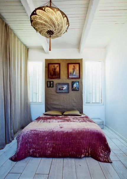 Curtain wall and burlap headboard with elaborate lighting above and a rustic cubrecama.