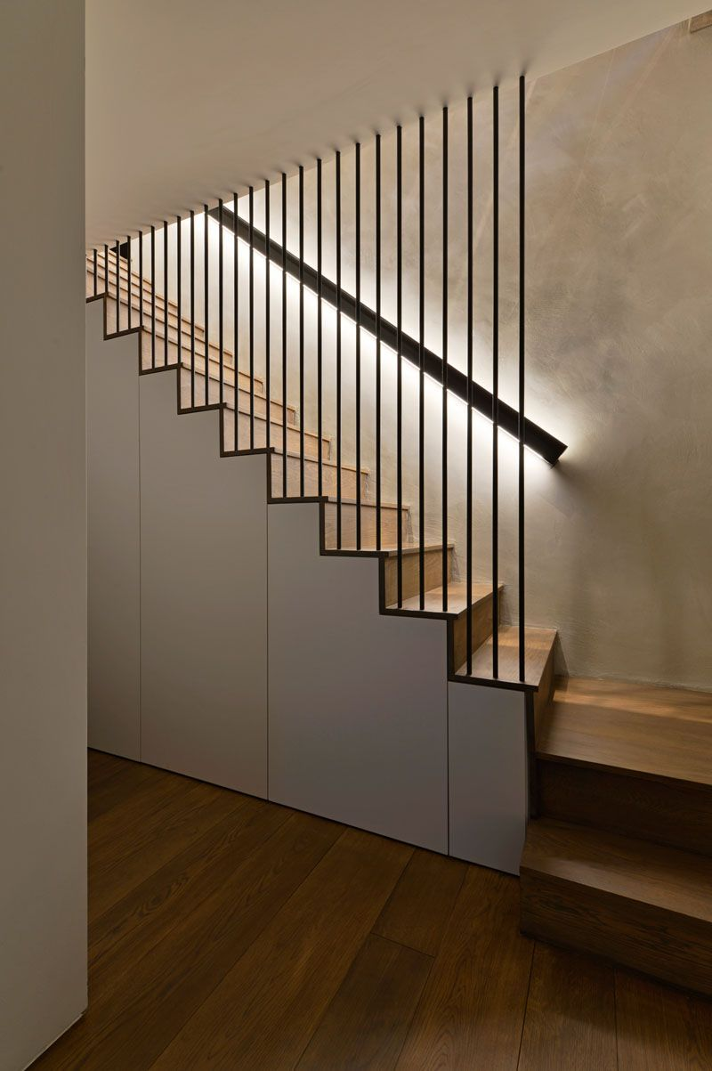 Design Detail – These Wood Stairs Have A Handrail With Hidden Lighting #lights These modern wood stairs have a handrail with hidden lighting, and a floor-to-ceiling steel rod safety barrier. #WoodStairs #Handrail #BacklitHandrail #modernhousedesigninterior