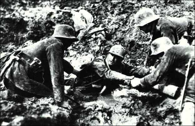 German soldiers rescue a French soldier from a shell hole