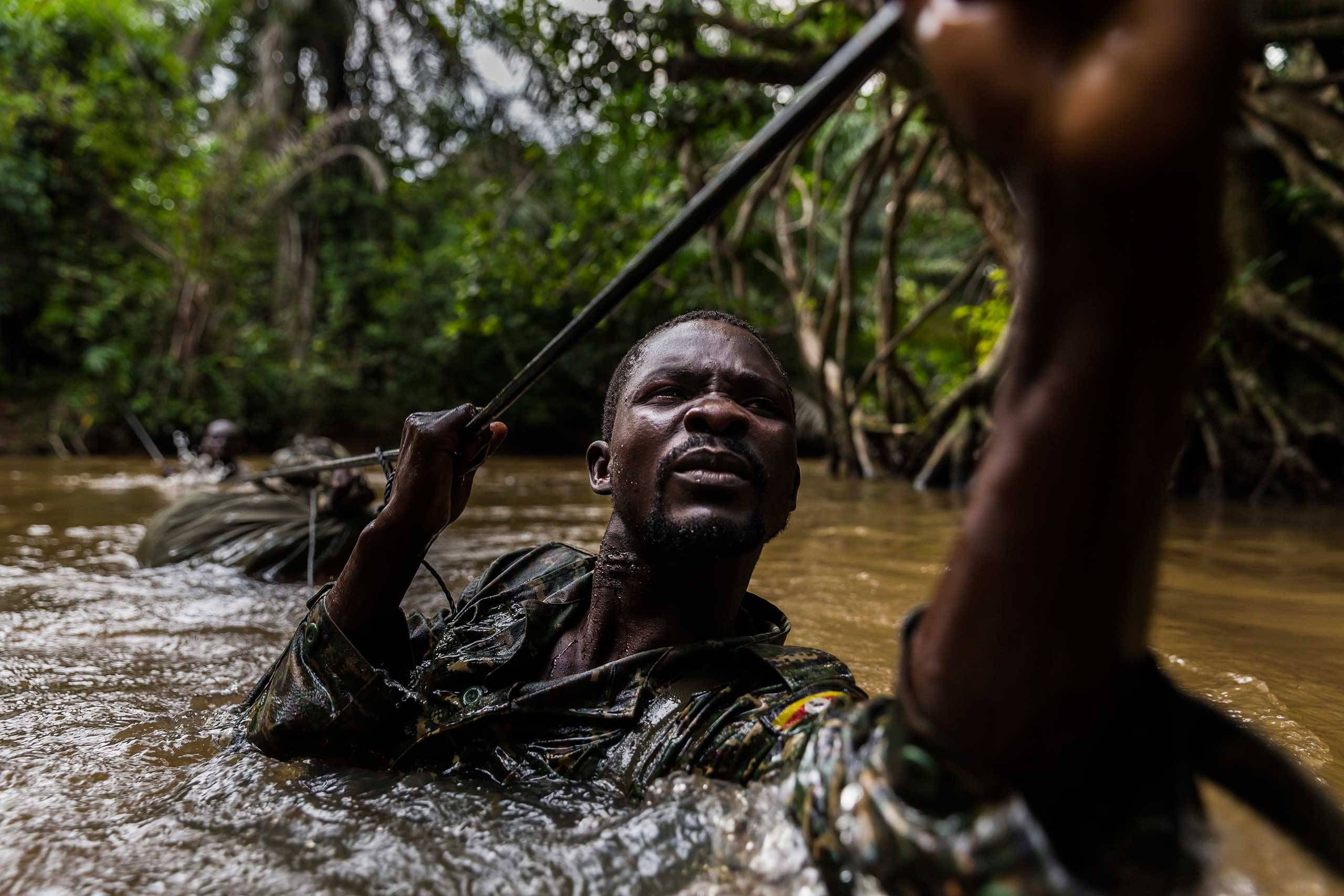 Ugandan soldiers cross a river while on patrol against the Lord's Resistance Army close to the border of the DRC. Mbeki, Central African Republic. Brent Stirton