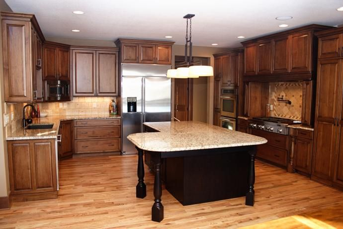 Painted black island cabinets, maple cabinets, site finish oak flooring, venetian gold light granite
