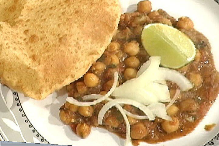 Channa Masala garnished with nimbu (lime) and pyaaz (raw onions) and served with poorie (fried puffed bread).  A typical street lunch!