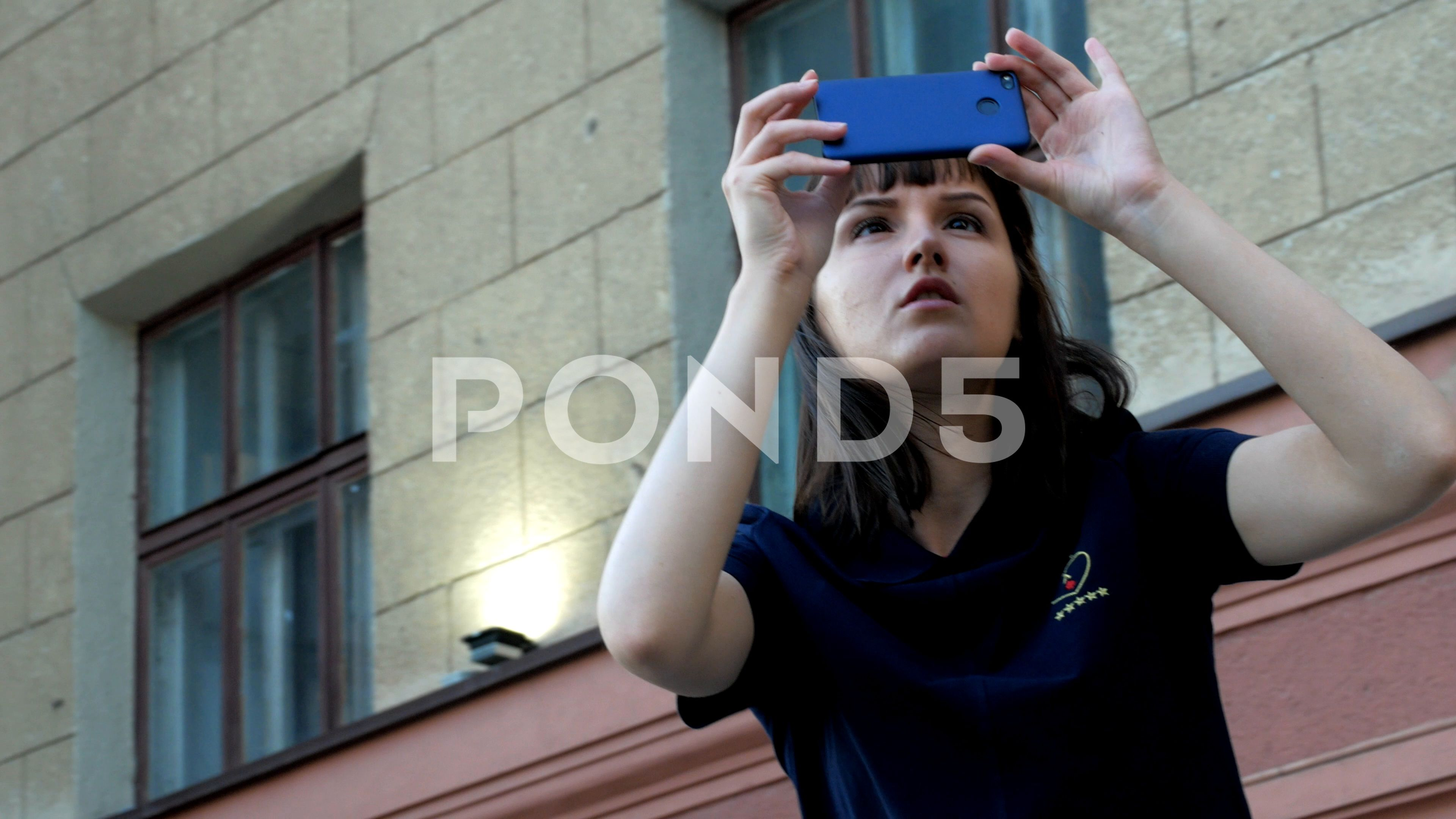 Beautiful Girl With Mobile Phone Shoots Video On The Street Stock Footage By Poberailo