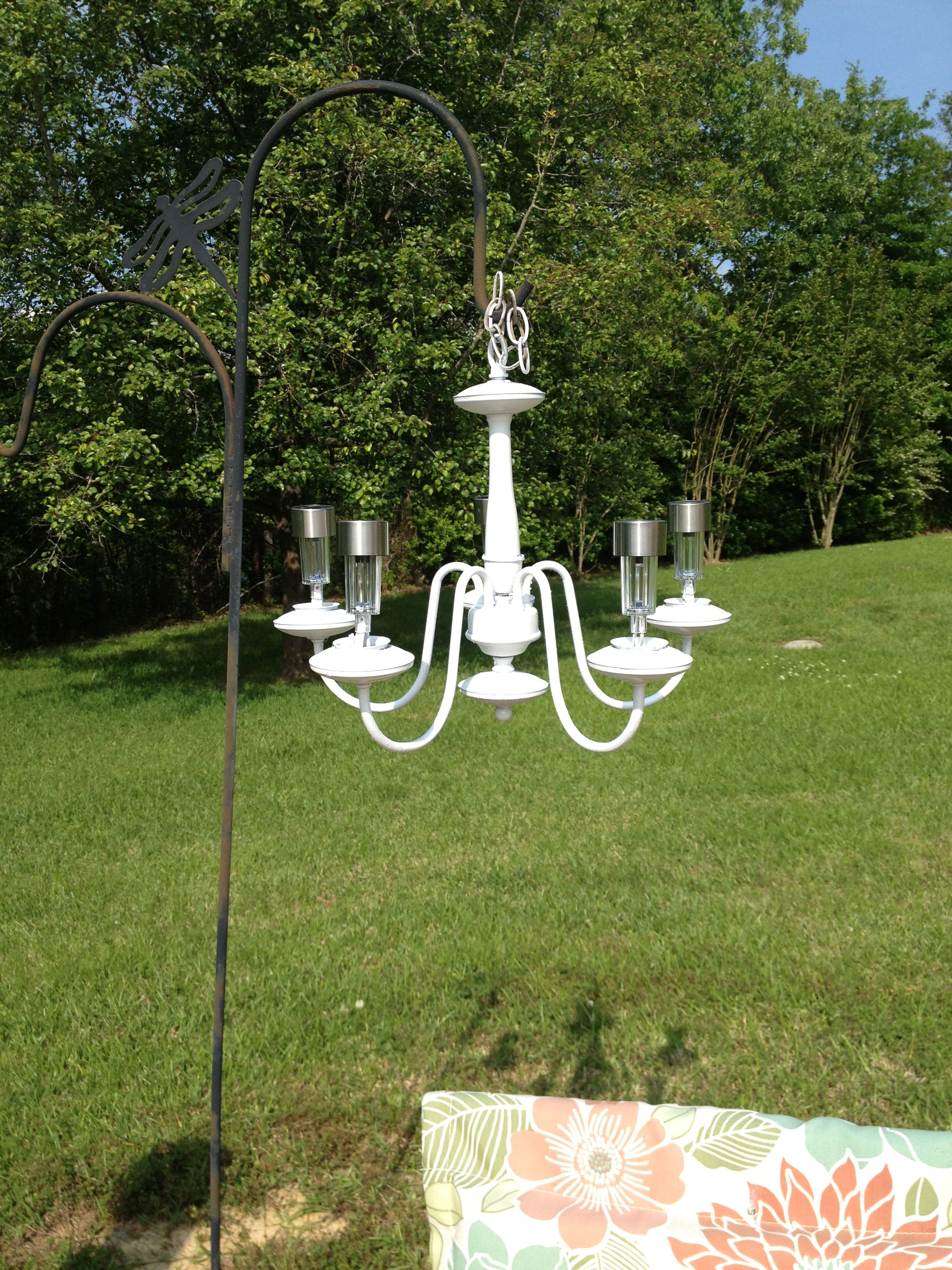 Spray paint an old chandelier and add solar lights to use outdoors