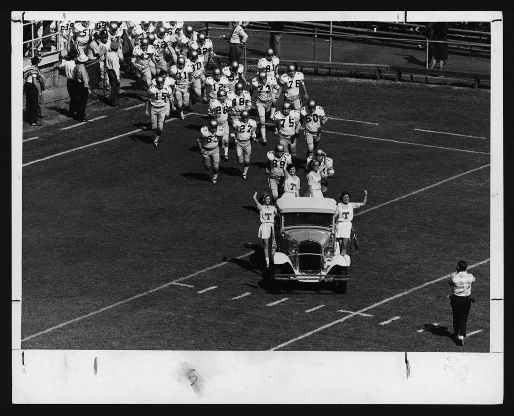 Ramblin' Wreck leading football team onto field, 1963