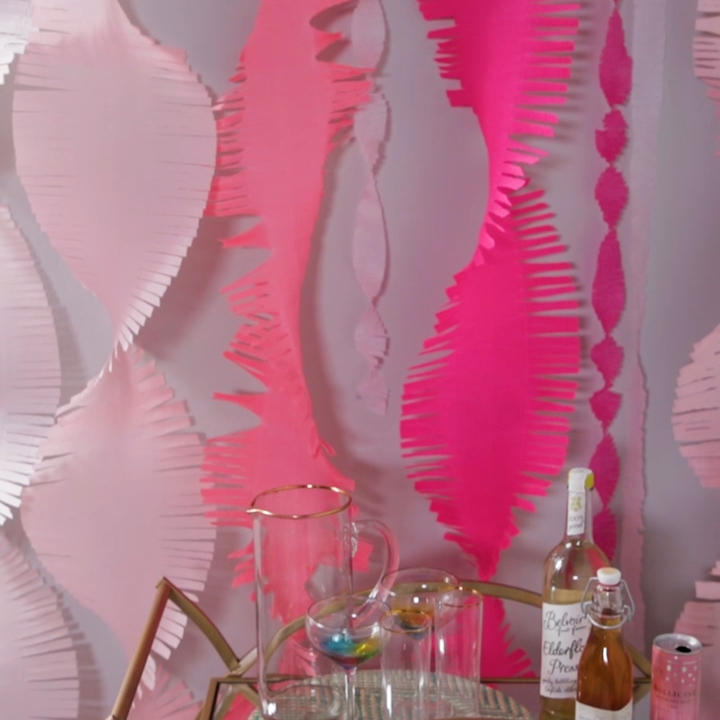Add a little something special to your next baby shower, birthday, or photo booth with these giant crepe paper streamers. The color possibilities are endless! #diytissuepaperstreamers #partybackdrop #diypartydecor #bhg