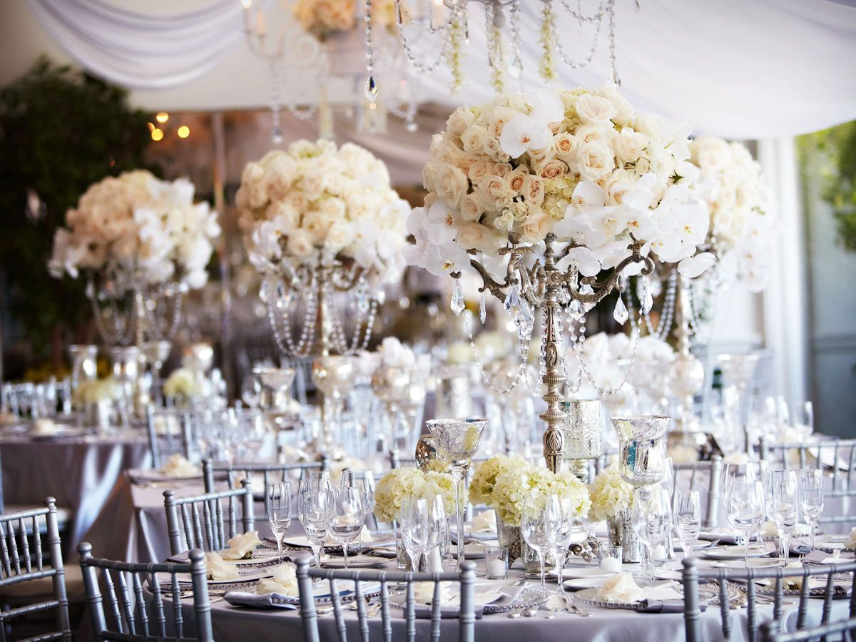 White wedding reception. Orchids, roses, and hydrangea centerpiece ...