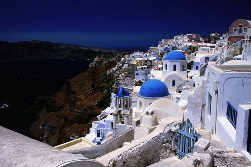Whitewashed houses and blue domes on cliff top are just so
