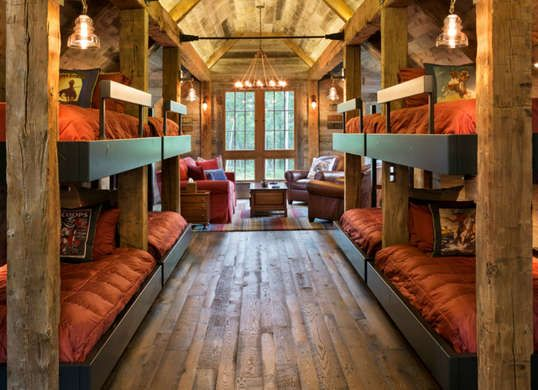 Rustic lodge style bedroom and sitting area with bare wood and bunk beds