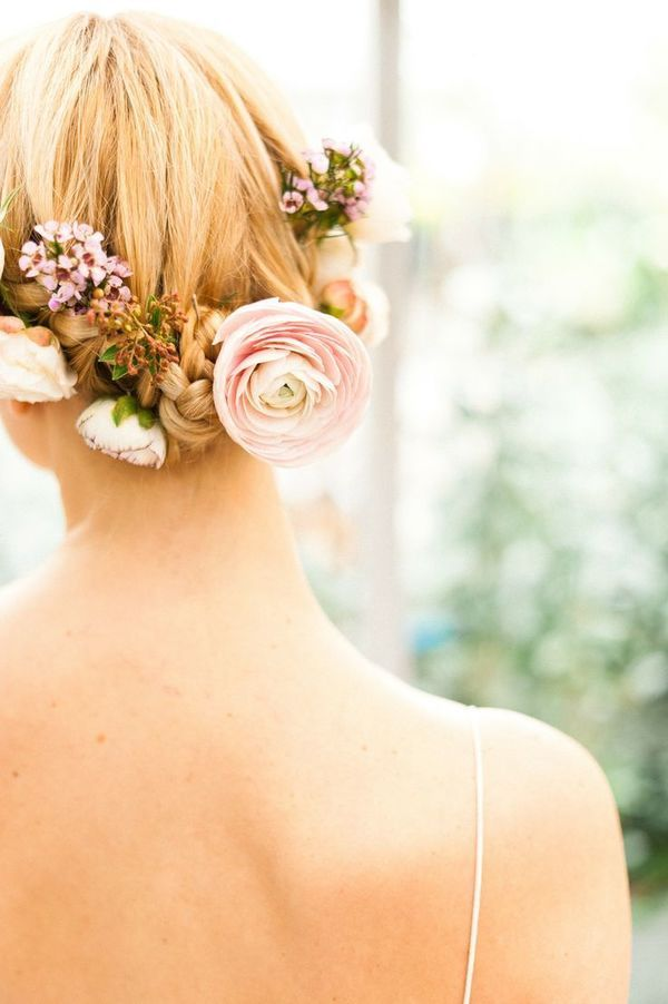 braided updo accessorized with flowers for brides with lob length hair