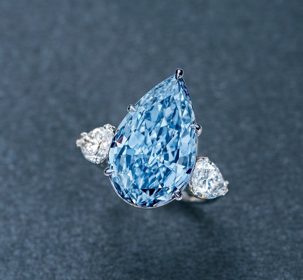 A MAGNIFICENT 8.26 CARAT FANCY INTENSE BLUE DIAMOND AND DIAMOND RING. Set with a pear-shaped fancy intense blue Type IIb diamond weighing 8.26 carats, flanked on either side by pear-shaped diamonds weighing 0.90 (D/VS1) and 0.98 carats (D/SI1), mounted in platinum. Estimate Upon Request // SOLD PRICE USD 15,406,080. GIA / Natural Fancy Intense Blue color, VS2 clarity, with excellent polish [POLY AUCTION HK - Magnificent Jewels - 2 OCT. 2017] #POLYAuction #FancyIntenseBlue #Diamond…
