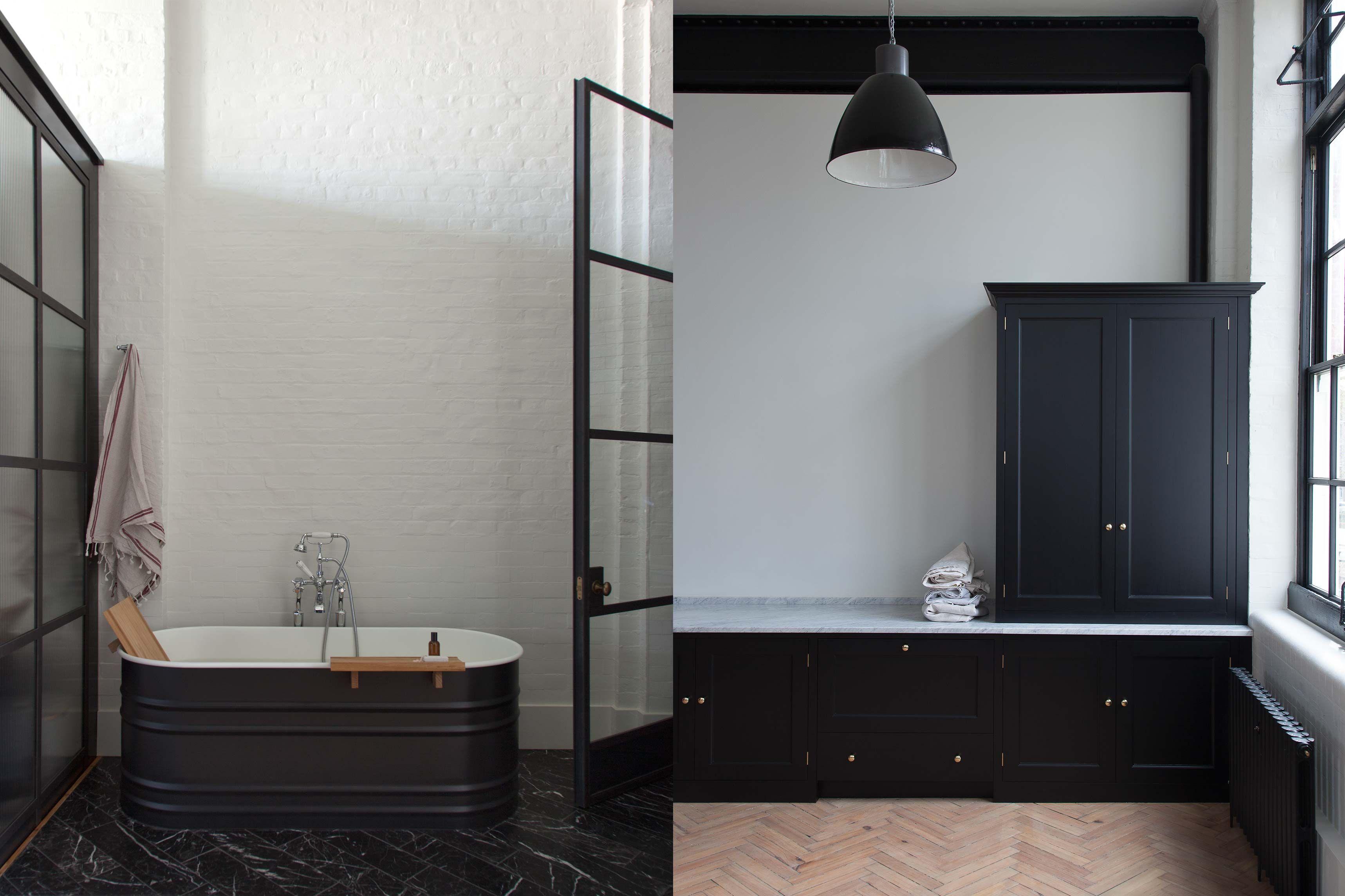 Victorian-style bathroom with tin bathtub and black cupboard units ...