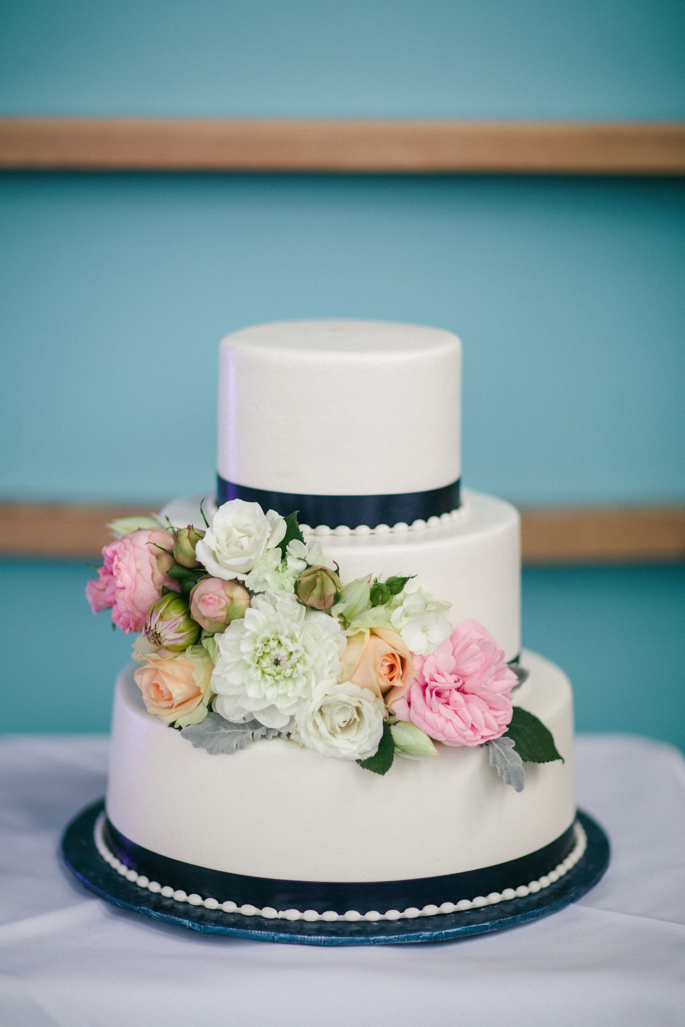 A smooth buttercream wedding cake with fondant pearl