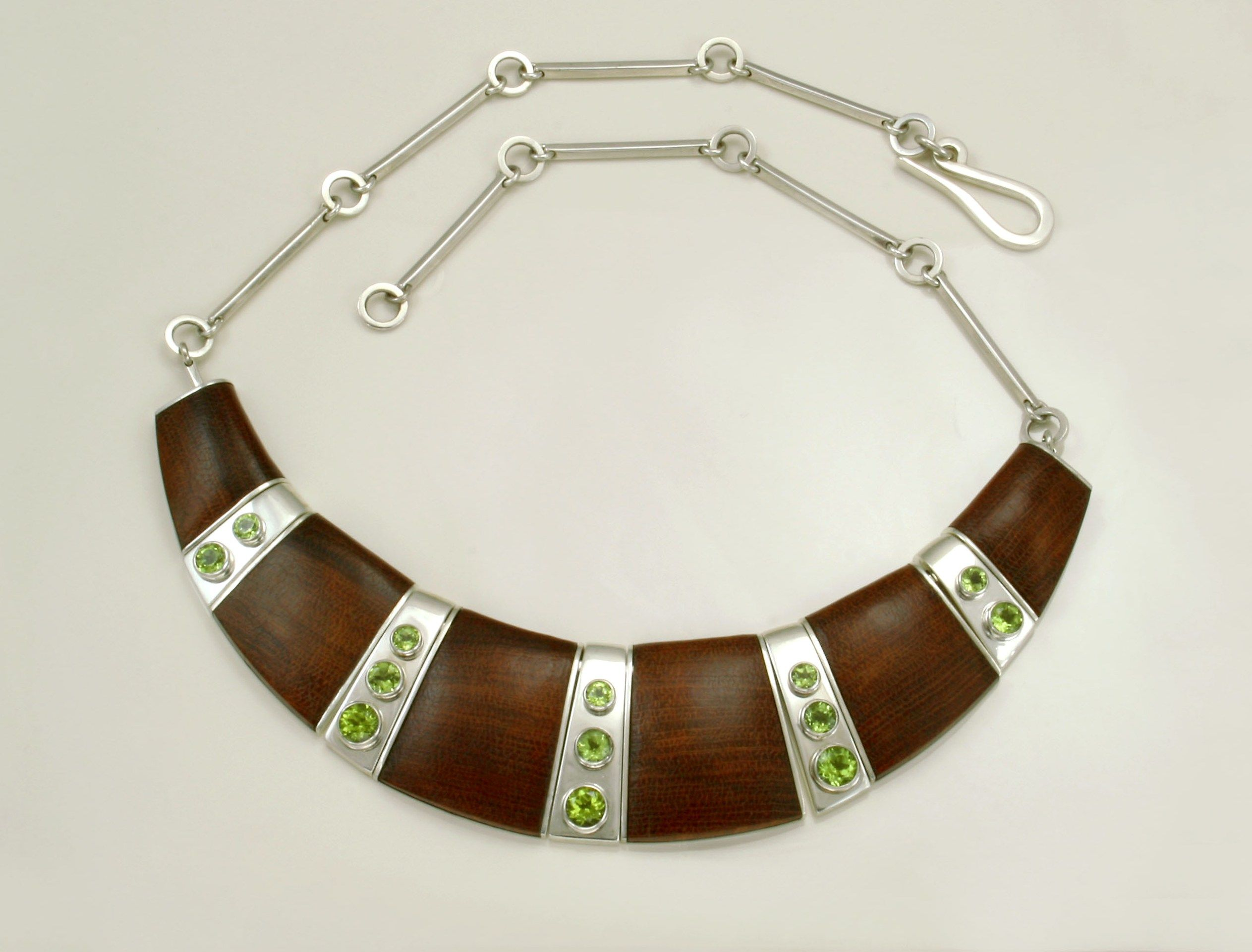 Necklace made of NZ native matai wood with peridots set in sterling silver.