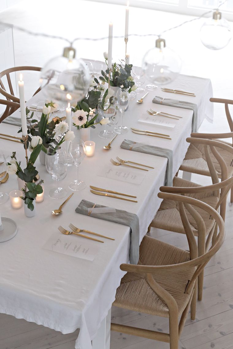 White vases on a white tablecloth, gold flatware, collection of vases, wooden seating