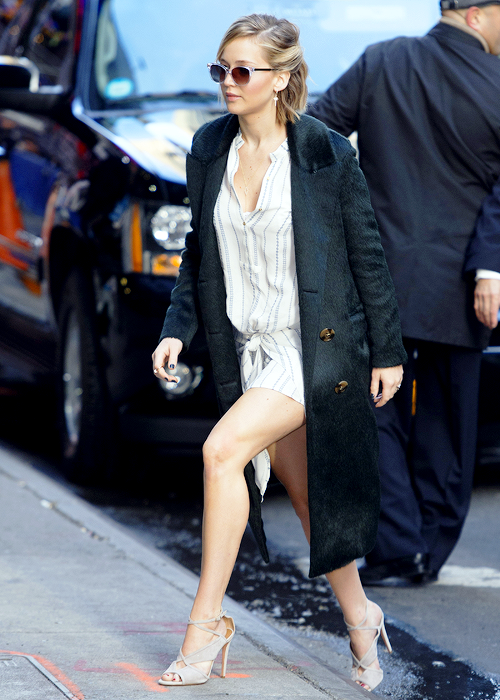 Leggy Jennifer Lawrence mounting the sidewalk in a shirt dress and strappy high heels.