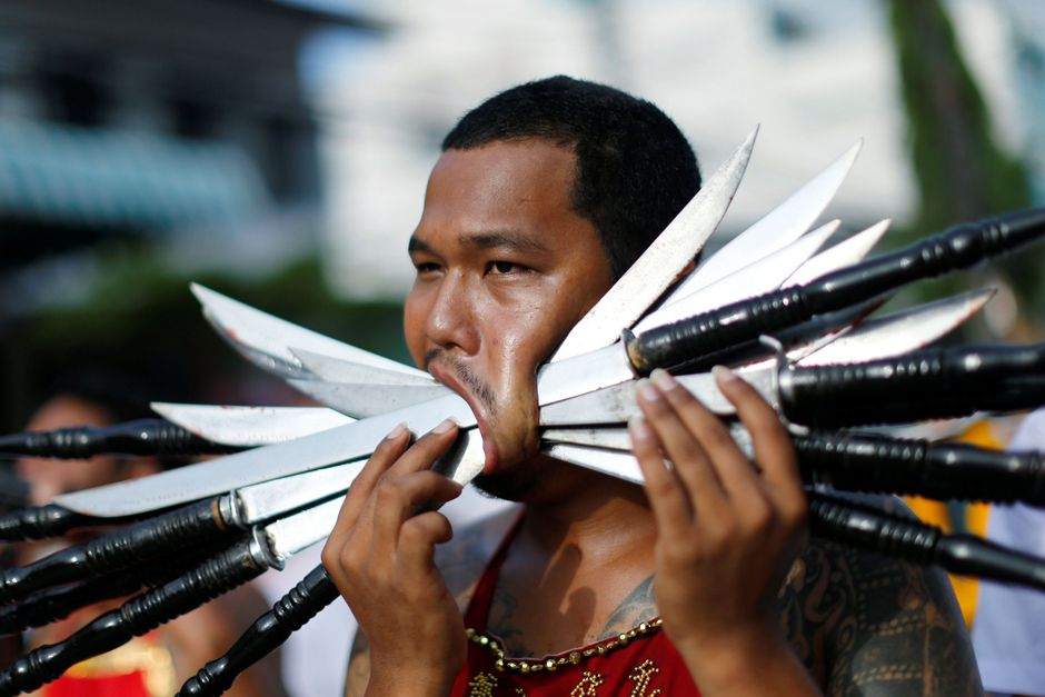 A devotee of the Chinese Samkong Shrine walks with knives pierced on his mouth during a procession celebrating the annual vegetarian festival in Phuket !! Oct-2016