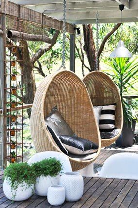Hanging wicker egg chairs on an outdoor patio