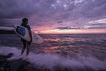 Junge Surferin steht vor dem Meer während eines Sonnenuntergangs, Sao Tome, Sao Tome und Príncipe, Afrika