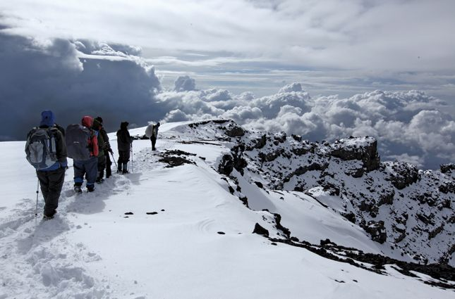 We could almost touch the clouds as they parted to reveal the descent before us to Crater Camp and Kili's full majesty. Even now, when I close my eyes, I still see her beauty.  Photo taken by Thomson Safaris guest, Helen Irving, during her Kilimanjaro trek via the Grand Traverse Route. The Grand Traverse was recently mentioned in Travel + Leisure's Hiking Guide!