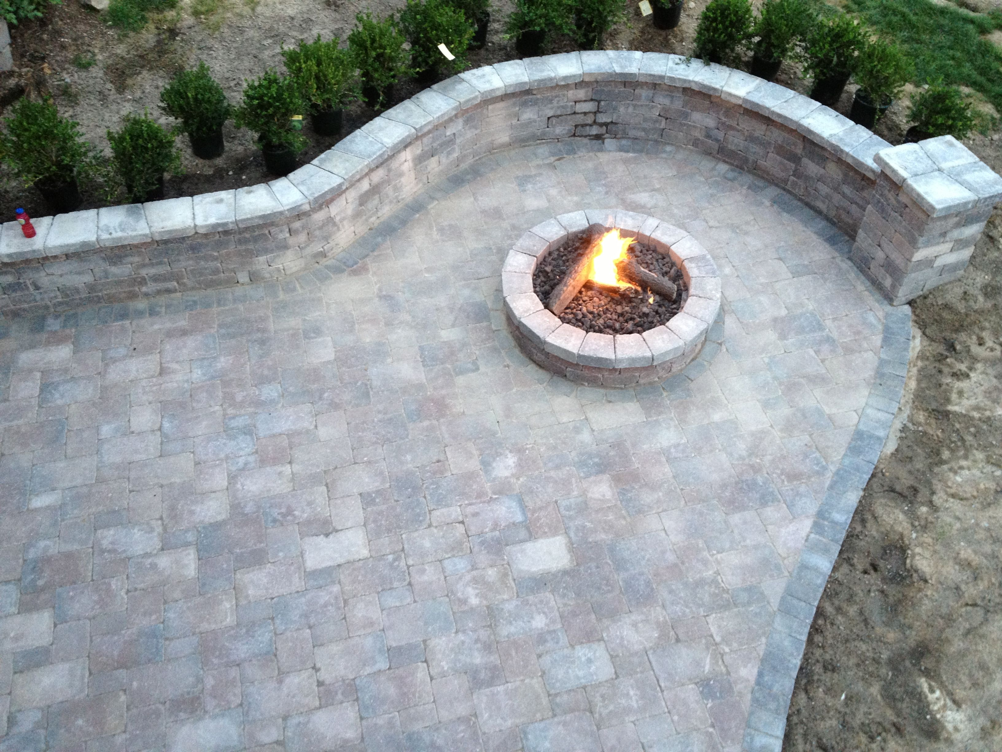 gas fire pit with tumbled unilock brick paver wall and pillar  design and creation by frank