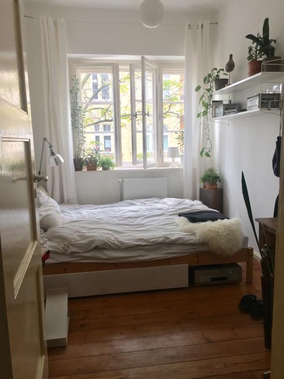 Schönes Altbau-Schlafzimmer mit Dielenboden und weißen Wänden