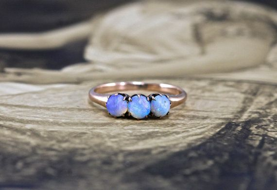 Circa 1900, this antique Victorian promise ring features three opal cabochons of an absolutely glowing blue-green shot through with hints of