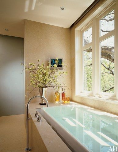 Travertine covers the master bath's walls and floor of this Toronto home by interior designer Powell & Bonnell and architect Murakami. The tub and fixtures are by Kohler | archdigest.com