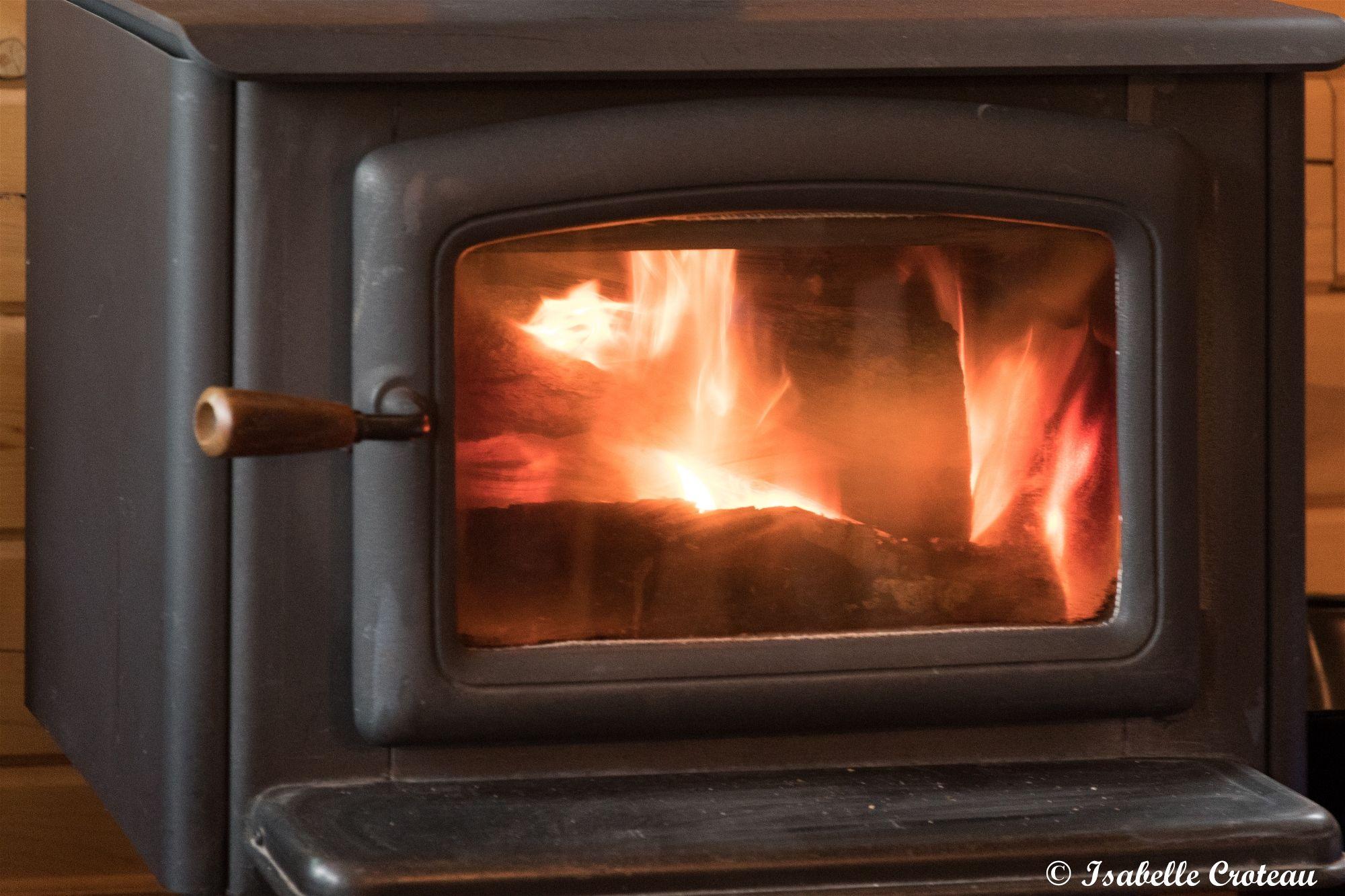 L'intérieur du Chalet le Malard.Le Poêle à bois agît aussi comme chauffage d'appoint par une froide nuit d'hiver | poêle à bois noir, poêle en fonte noir, porte en vitre trempée, feu, poignée de bois
