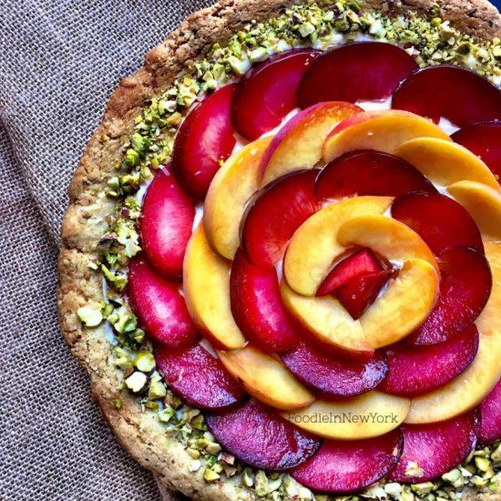 A pistachio-almond tart layered with honey-sweetened mascarpone and topped with fresh peaches and plums