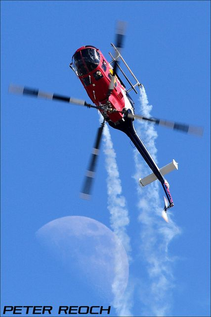 "This great shot of the Red Bull helicopter ""going over the top"" at AirVenture 2012 is called ""Moon Wings."" Photo by Peter Reoch Photography, via flickr."