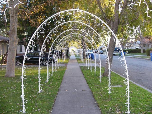 lighted arches made out of 12 inch pvc pipe held in place by 3 foot rebar stakes each arch is 10 feet tall and 8 feet wide with 300 lights on each