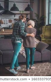 Sons support. Young man in jeans supporting his mom #aging, #aging lady, #apartment, #at home, #bearded, #caring son, #caucasian, #checkered shirt, #comfortable, #domestic life, #family, #feeling bad, #grey-haired, #handsome, #hardly walking, #helping, #holding, #holding hand, #home, #illness, #indoors, #loft, #loving son, #man, #mom, #mom and son, #mother, #nursing, #rehabilitation, #sick, #sick woman, #son, #support, #visit to mom, #weak, #woman, #young adult, #young man