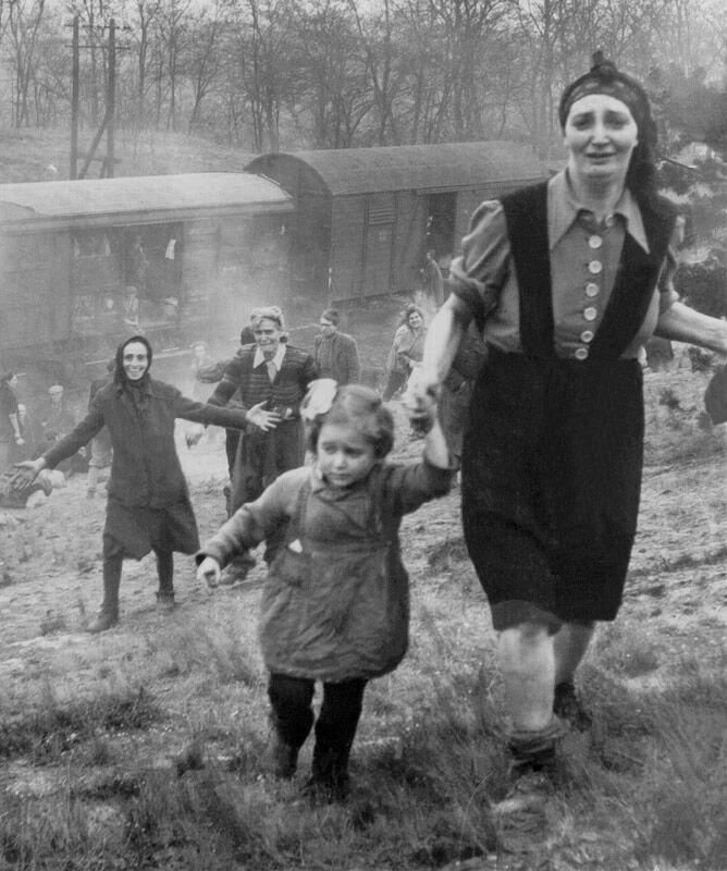Refugiados judeus caminhando em direção às tropas aliadas durante a Segunda Guerra Mundial. Neste momento, eles tinham acabado de perceber que haviam sido libertados do comboio que os levaria até um campo de concentração nazista. Abril de 1945.